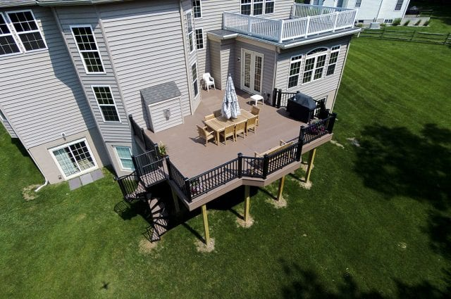 deck with a spiral staircase and post cap lighting