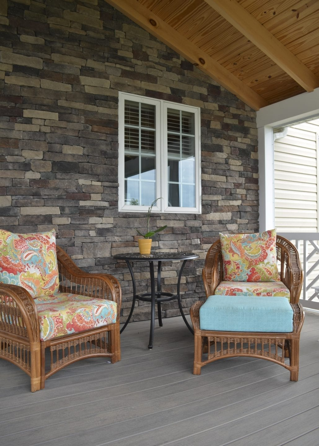 screened-in porch with stone wall