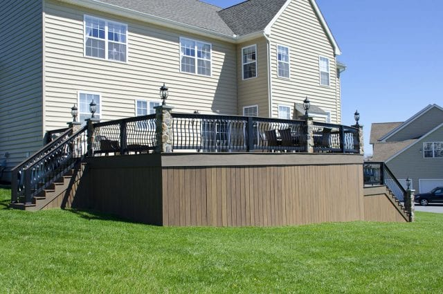 deck with stone columns and perimeter lighting