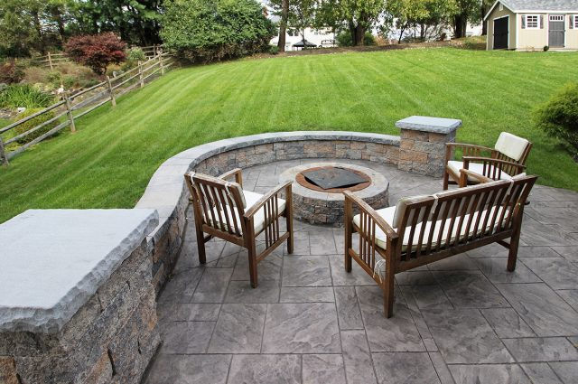 Stamped concrete patio with techo bloc sitting wall and fire pit in west chester pa